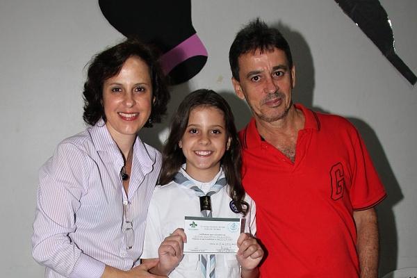 Letícia com o certificado de investidura ao lado de seus pais